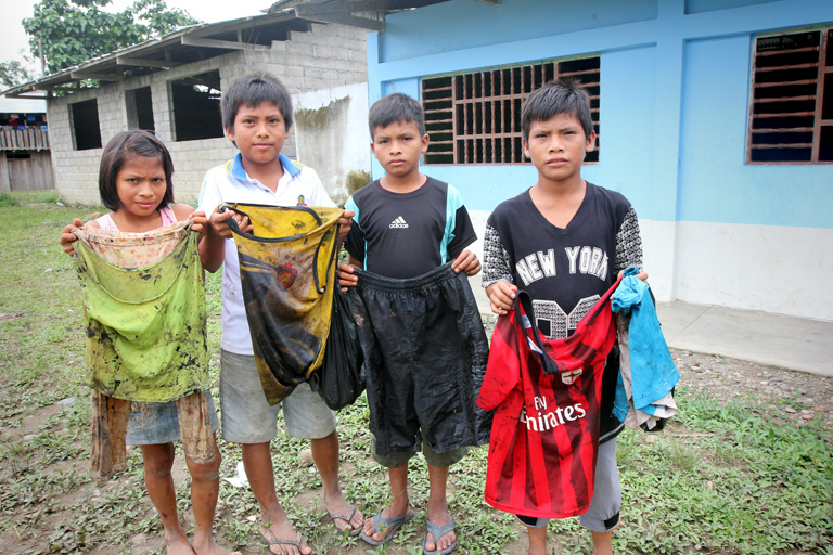 Children in Nazareth, a village at the confluence of the Chiriaco and Marañón rivers in northern Peru, show the clothes they wore when they scooped crude oil out of the Chiriaco River after a pipeline spill. Photo by Barbara Fraser.