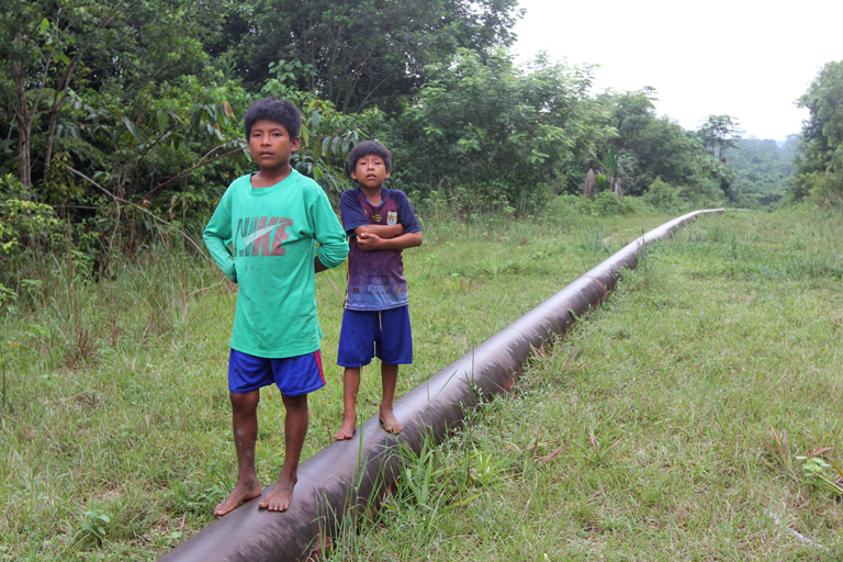Children walk along a spur of Peru's main oil pipeline near the village of Mayuriaga, where a spill in February affected more than 20 communities along the Morona River. Photo by Barbara Fraser