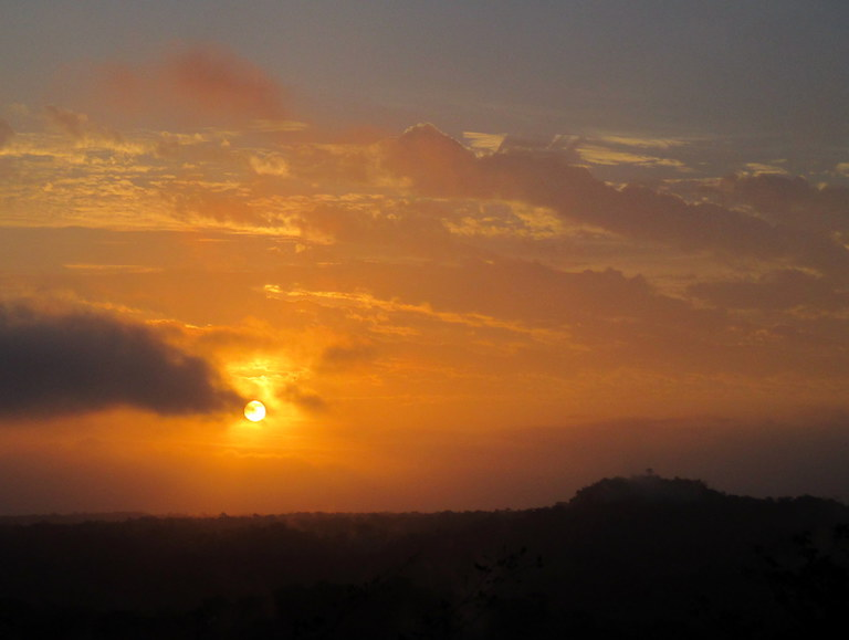 The sun rises over the seemingly endless jungle in Guatemala's Maya Biosphere Reserve. To the right, the top of the massive La Danta pyramid juts out above the canopy. Photo by Sandra Cuffe.