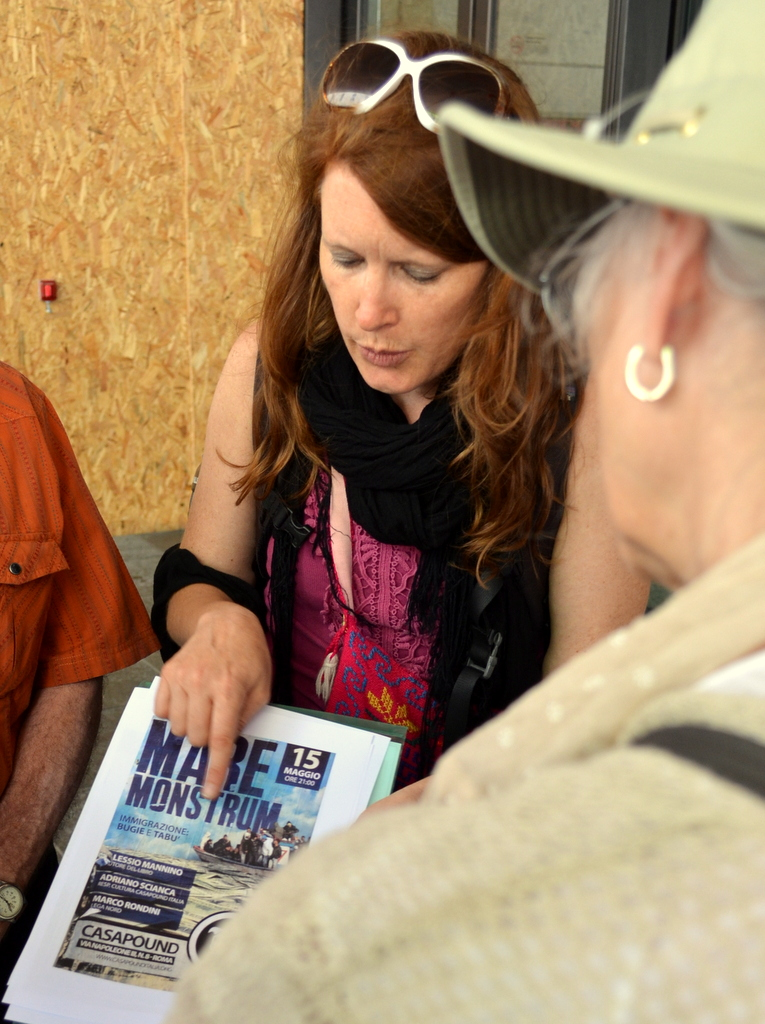 JRS official Jill Drzewiecki shows Emmylou Harris a xenophobic poster seen around Rome. Photo by Justin Catanoso