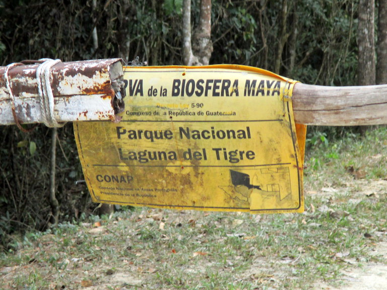 A makeshift barrier gate crosses the road at a CONAP-staffed checkpoint for the eastern area of the Laguna del Tigre National Park. Photo by Sandra Cuffe.