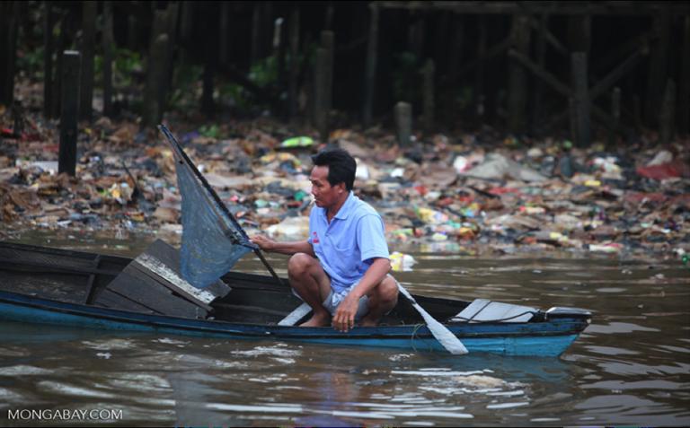 A man fishes near an illegal trash dump in Banjarmasin, Indonesia. Photo by Rhett Butler.