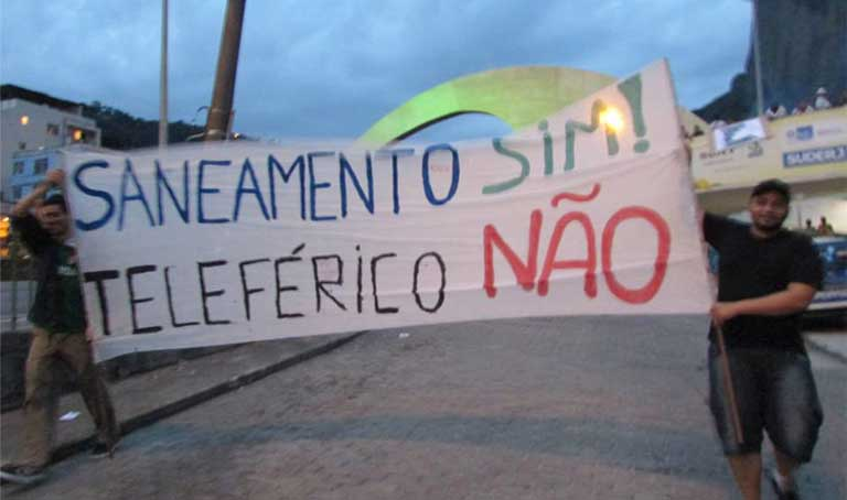 "Protest banner: Residents make their priorities clear with this banner during a joint protest organized by the Rocinha and Vidigal favelas in Rio de Janeiro. The banner reads: ""Sanitation Yes! Cable car No! "" Photo by Melaina Spitzer, Catalytic Communities"