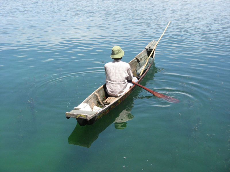 A fish farmer uses a small canoe to check his floating cages in Indonesia's Lake Toba, in North Sumatra province. Photo by isawasi/Flickr