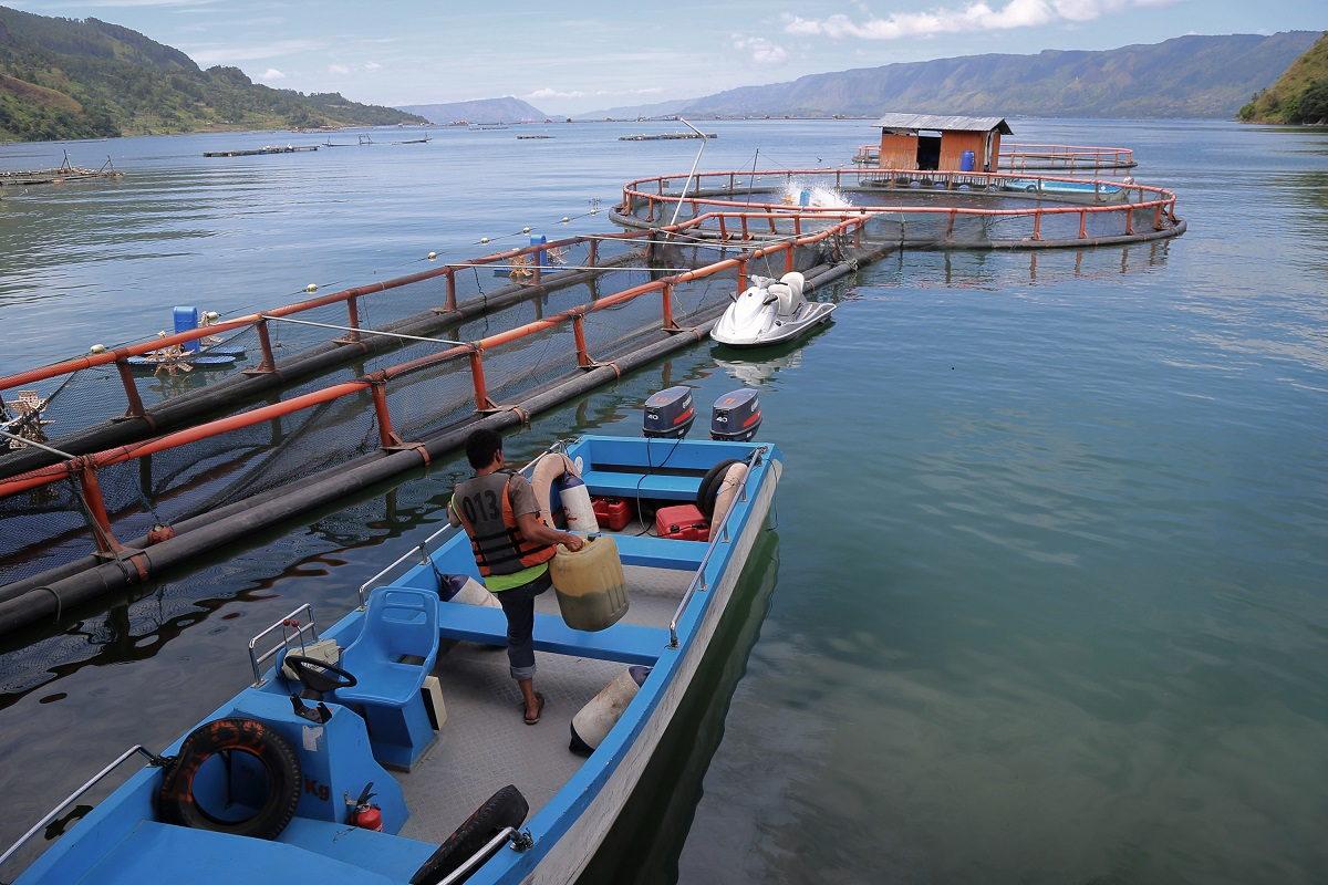 A boat seen next to a fish pen in PT Suri Tani Pemuka's farming site in Tambun Rea, Simalungun district