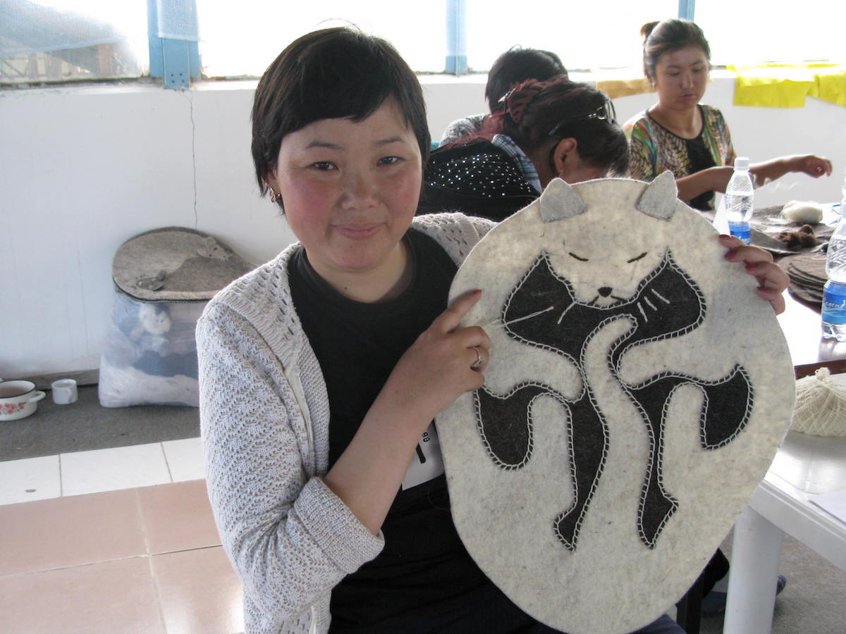 A Kyrgyz woman holds a pet mat, one of the products produced through a program that aims to both improve women's incomes and encourage communities to conserve snow leopards. Photo courtesy of the Snow Leopard Trust