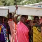 Tanzanian women carry new beehives into the forest. Photo by Felipe Rodriguez/APW