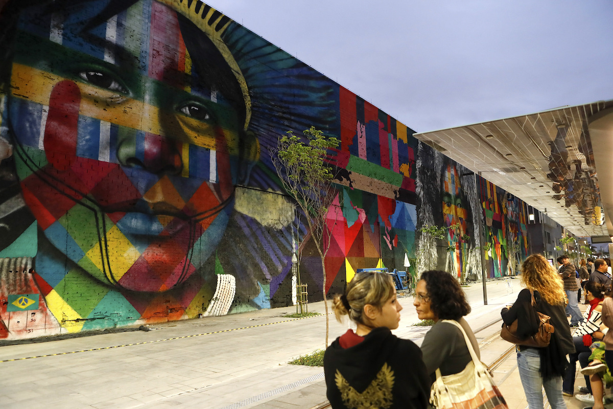 Etnias, a 620-foot long mural in Rio de Janiero, Brazil, representing indigenous people from five continents by Brazilian artist Eduardo Kobra. The mural was commissioned for the Olympics. Photo by Agência Brasil Fotografias.