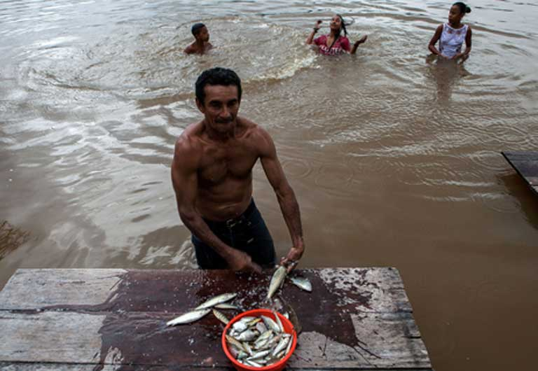 A man cleans fish, while others play in the river. Photo by Lilo Clareto/Repórter Brasil