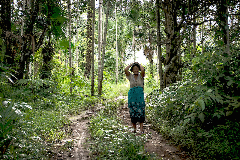 A women returns from the forest after a day at work. Photo by Katie Arnold