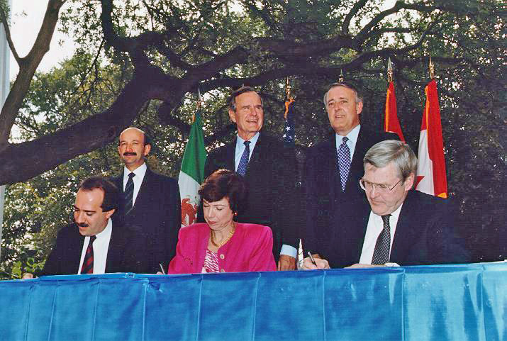NAFTA Initialing Ceremony, October 1992. From left to right (standing) Mexican President Carlos Salinas de Gortari, US President George H. W. Bush, Canadian Prime Minister Brian Mulroney. (Seated) Jaime Serra Puche, Carla Hills, Michael Wilson. Photo courtesy of UNCTAD