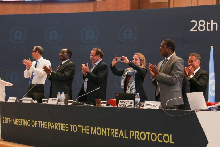 Delegates applaud the adoption of the Kigali Amendment to the Montreal Protocol, which will reduce hydrofluorocarbon usage worldwide by 80 to 85 percent by 2047. Photo by IISD/ENB | Kiara Worth