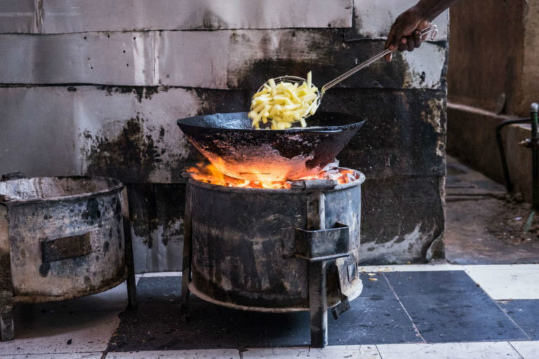 A cook fries potato chips using charcoal at the Salama Guest House on the Kenyan side of Namanga. Photo by Nathan Siegel