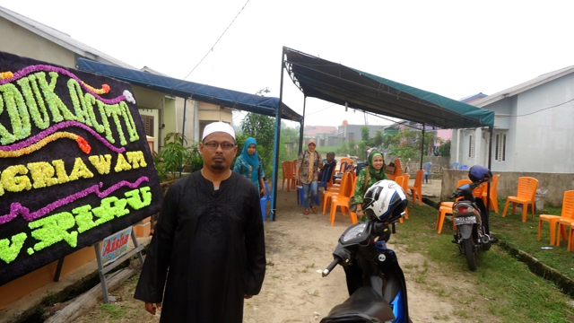 Mukhlis stands outside his home in Riau last year as mourners gather for his daughter. Photo by Made Ali