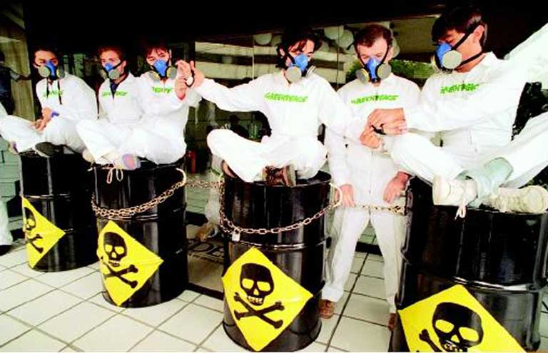 Greenpeace members handcuffed together and sitting on steel drums similar to toxic waste drums outside of the Mexican Office of Environmental Protection, calling attention to the toxic waste disposal facility at Guadalcazar, San Luis Potosi, owned by the U.S. company Metalclad Corporation, Mexico City, Mexico, July 19, 1995. Photo compliments GreenPeace Mexico