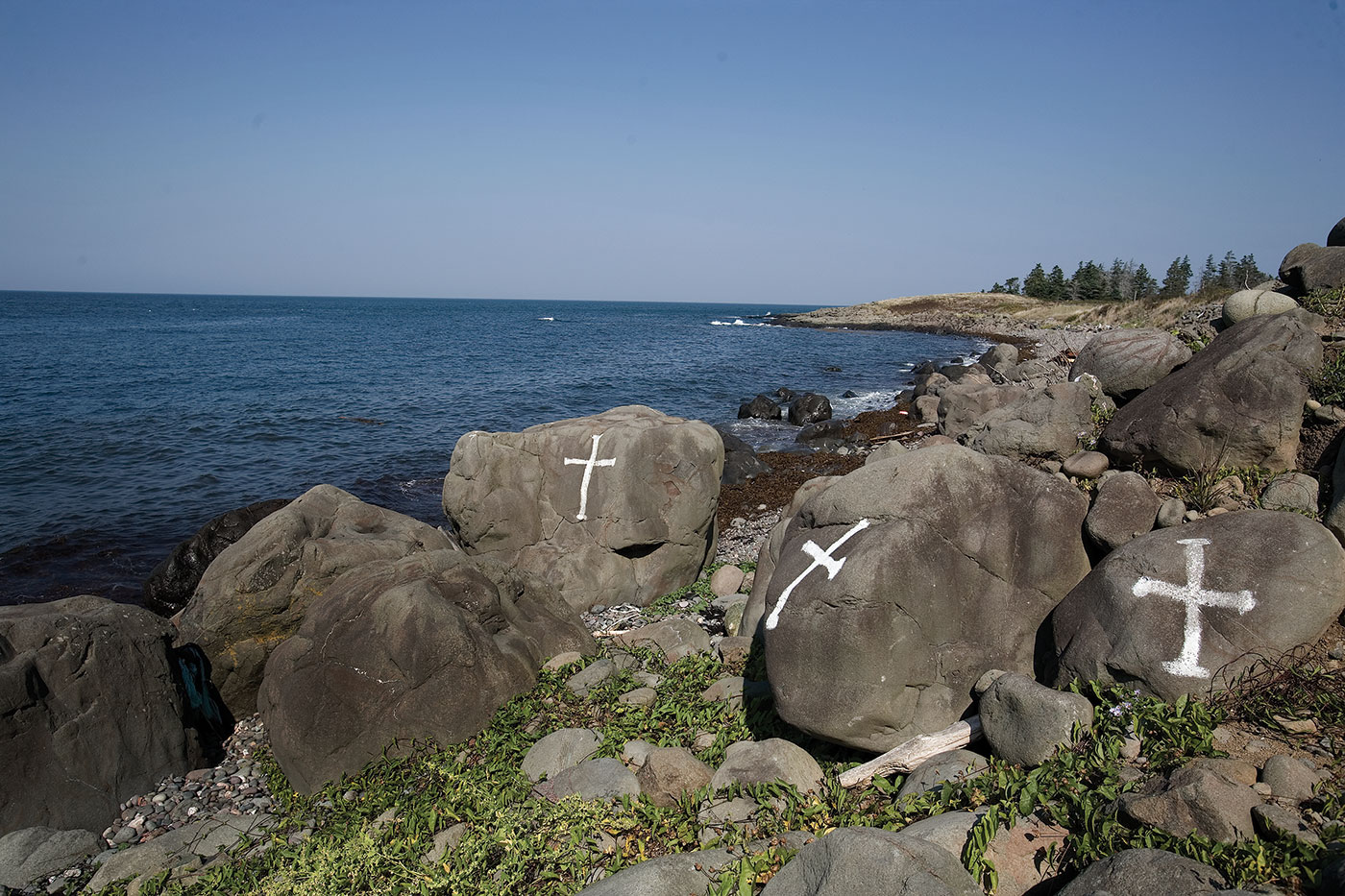 Crosses painted on rocks near the proposed Bilcon marine terminal site. The local community protested loudly against Bilcon's quarry and industrial seaport proposal. Photo by Kemp Stanton licensed under the Creative Commons Attribution-Share Alike 2.0 generic license