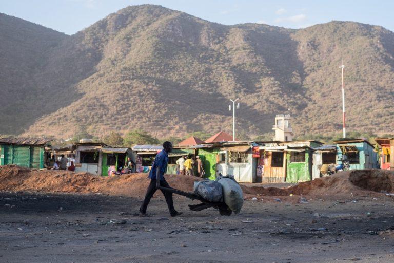 A man transports charcoal in a wheelbarrow in No Man's Land in Namanga, a border town between Kenya and Tanzania. Photo by Nathan Siegel