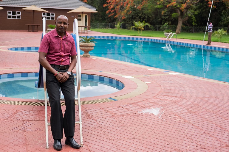 Stanley Le Shao, manager of the Namanga River Lodge, poses for a portrait in front of the hotel's newly renovated pool. Photo by Nathan Siegel