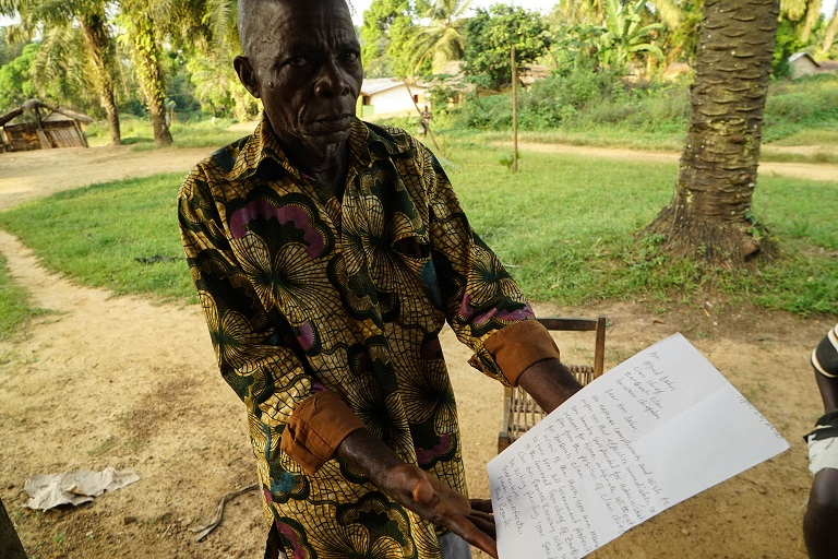 Alfred Dahn, a chief elder in Garwin, holds a copy of the MOU that he refused to sign. Photo by Ashoka Mukpo for Mongabay.