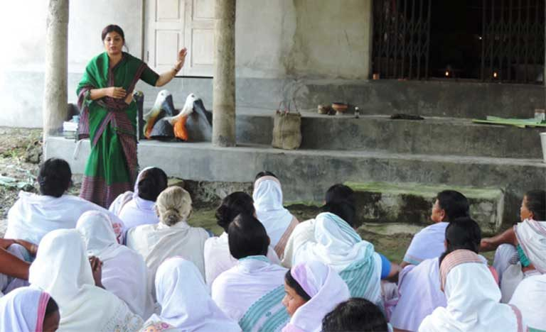 Purnima Barman speaks about Greater Adjutants to women at a village temple. The women have honored the bird that they now protect by adding it to sacred songs. Photo courtesy of Aaranyak
