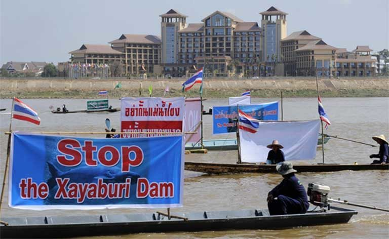 Villagers in Thailand protest the construction of the Xayaburi Dam on the Mekong River during the Asia Europe Summit in Vientiane, Laos in 2012. Very often protests signs used by environmental groups against large infrastructure projects feature both a country's native language and also English, so that if the demonstration gains coverage by the international press the message will get easily communicated to the English-speaking world. Photo by Pianpron Deetes / International Rivers CC-BY-NC-SA 2.0 (Flickr)