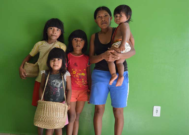 Tamawaerw Paracanã and her family. Besides the small income she earns from the crafts she makes and sells, their only income is the 200 Reals (approximately US $59) per month provided by the Bolsa Familia government subsidy program. Tamawaerw's husband has been unable to find work in the city of Altamira where the family was relocated when the dam was built. Photo by Zoe Sullivan
