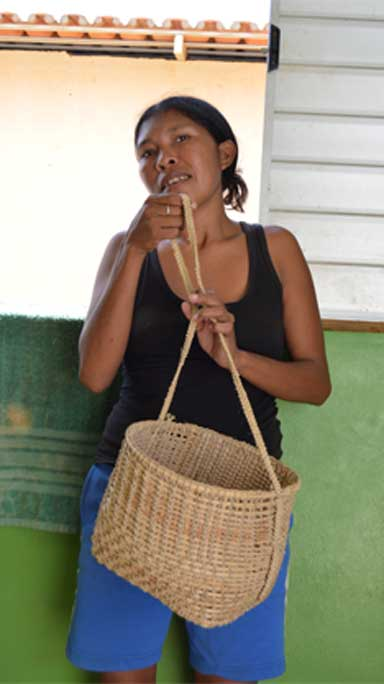 Tamawaerw Paracanã stands by the window of the resettlement home her family obtained after a long-fought battle with Norte Energia, the consortium that built and operates the Belo Monte dam. She shows off a hand-woven bag. Paracanã makes these bags and other crafts to sell. Photo by Zoe Sullivan