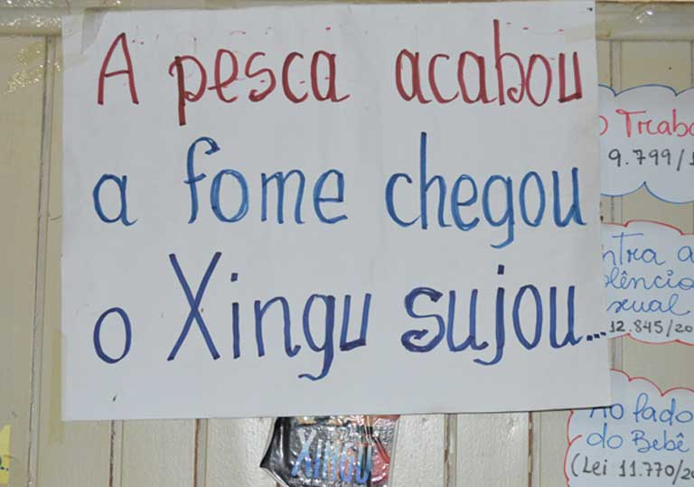 "A placard in the office of Xingu Vivo, an environmental advocacy NGO. It reads: ""The fishing ended, hunger arrived, the Xingu got dirty."" Photo by Zoe Sullivan"