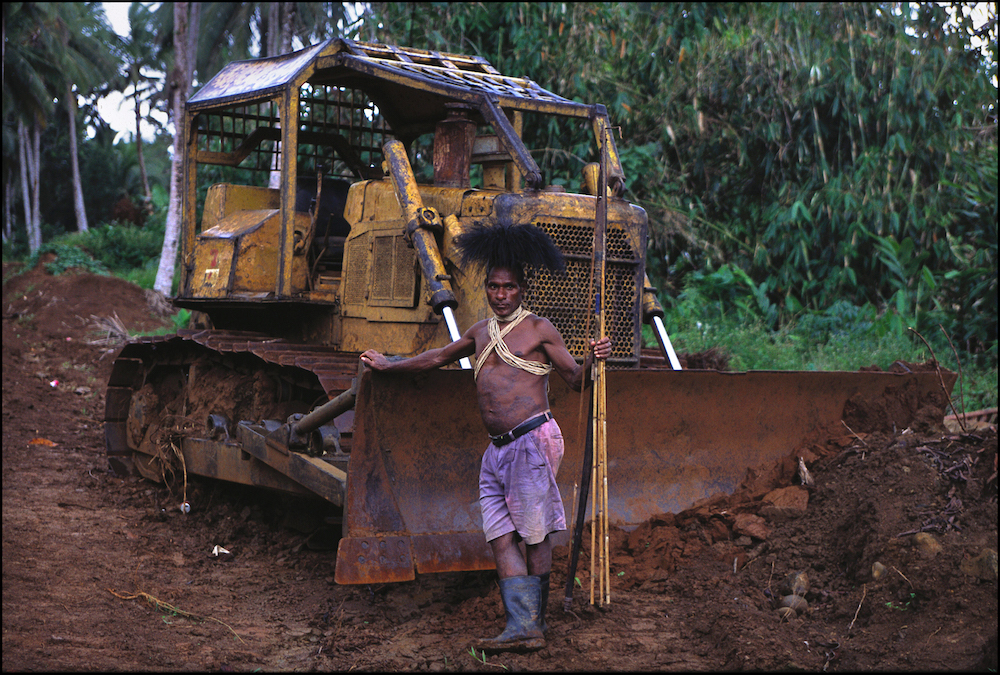 Customary landowner Auwagi Sekapiya of the Ubei Clan; Kosuo tribe. Photographed here in 2003 in front of a bulldozer, he was angry that a logging road destroyed his sago swamp. Photo courtesy of Sandy Scheltema/Greenpeace.