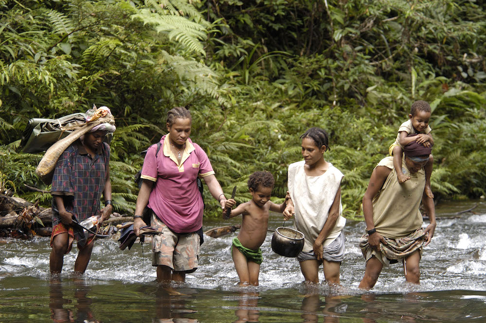 Women crossing a river on the way to Mt. Bosavi in Southern Highlands Province. Photo courtesy of Marcus Mauthe/Greenpeace.