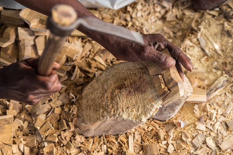 A woodcarver makes a carving of a rhinoceros on the outskirts of Lunga Lunga, a town on the border between Kenya and Tanzania. Photo by Nathan Siegel for Mongabay