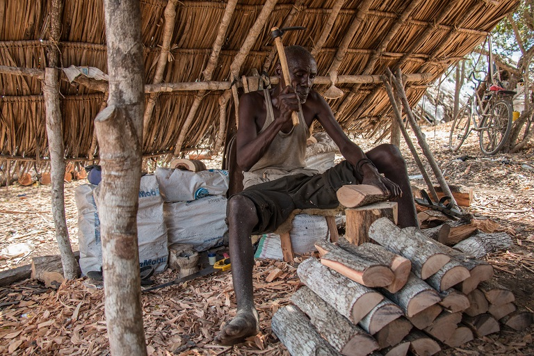 A woodcarver cuts logs imported from Tanzania that will be used to make carvings for tourists on the outskirts of Lunga Lunga, a town on the border of Kenya and Tanzania. Photo by Nathan Siegel for Mongabay