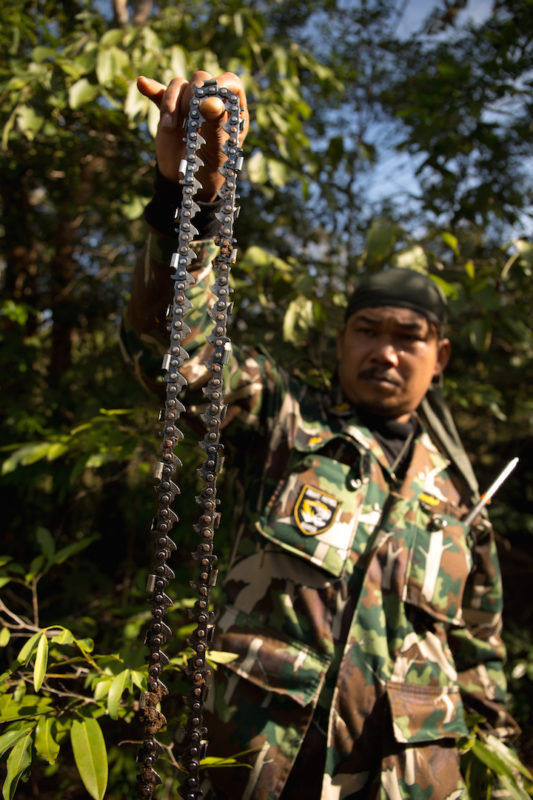 Ranger Salak Chairacha holds up a saw discarded by illegal loggers operating in Thailand's Thap Lan National Park. Photo by Demelza Stokes.