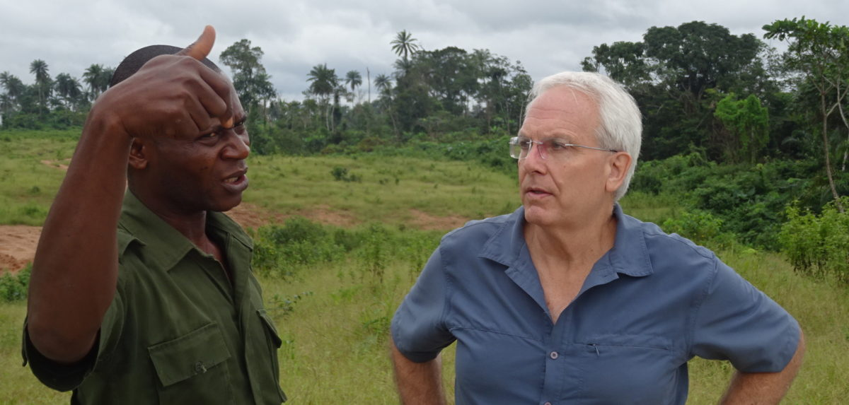 Laurance (right) getting a brief from a park guard about a planned superhighway in Nigeria. Photo by Mahmoud Mahmoud.
