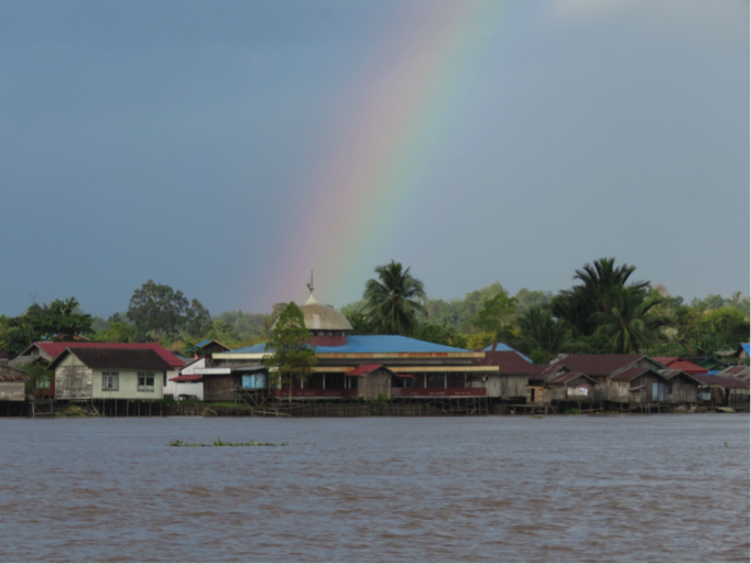 Rays of hope over a densely settled Mahakam river bank. Photo by Gabriella Fredriksson.