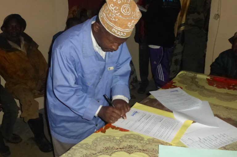 Abdourahamane signing the first agreement to preserve the Livingstone roost site at the mayor's office in Adda in the presence of village leaders and the village forest management committee. Photo credit: Dahari.