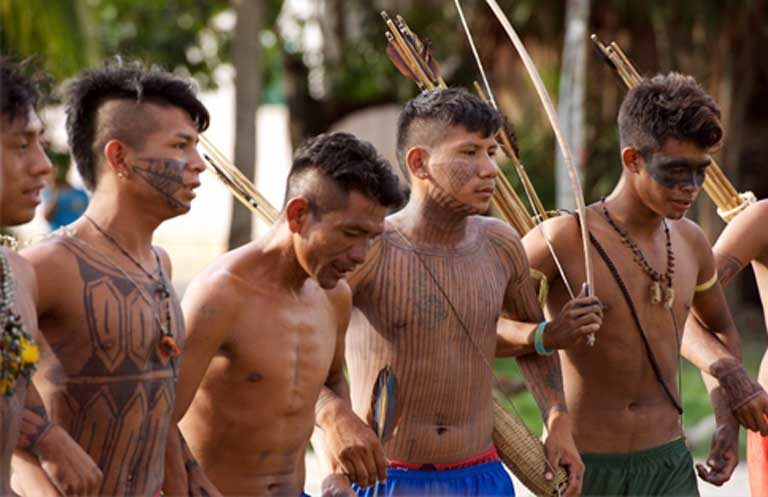 Dancing Munduruku warriors, with ceremonial face paint used to welcome village visitors. This traditional face paint design was mistakenly perceived by the Federal Police as war paint. Photo by Mauricio Torres