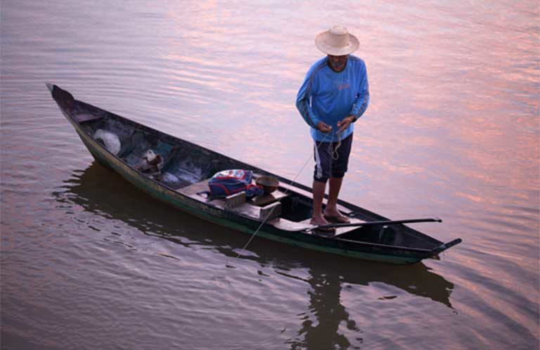 Early morning fishing on the Teles Pires River. River communities depend on fish for their diet and income. The Teles Pires dam is altering river temperatures and flow, concentrating agricultural pollutants, and has closed off migratory fish routes — all of which is harming the fishery. Despite that, the company that built the dam has won several sustainability awards. Photo by Thais Borges