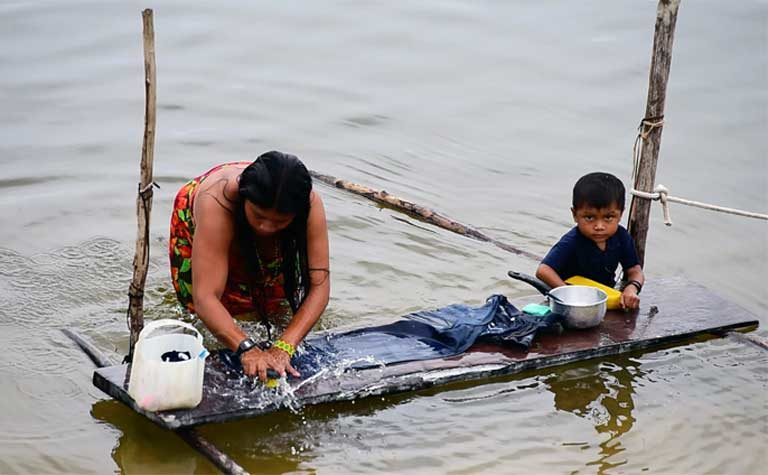 An indigenous woman washing a carpet in the Teles Pires River. The Munduruku and other indigenous groups rely on the river for everything — for work and play, as livelihood and a transportation corridor. The Teles Pires dam has negatively impacted many of these activities. Photo by Thais Borges
