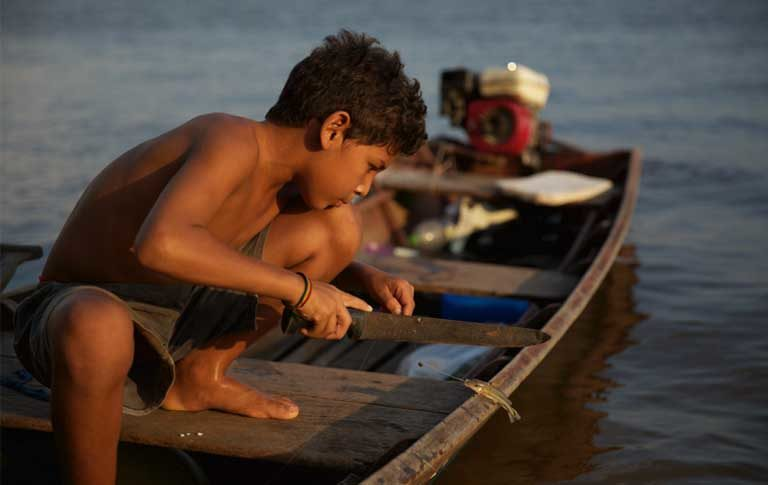 An indigenous boy fishing. The Munduruku report that the construction of the Teles Pires dam has damaged their fishery. Photo by Thais Borges