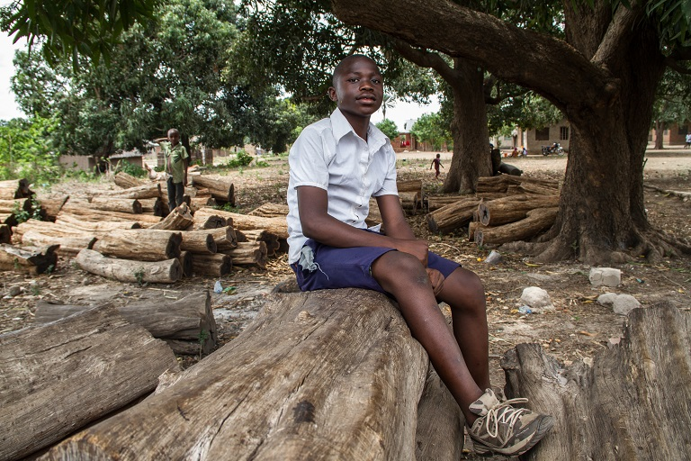 A village student sits atop a pile of mpingo logs in his school uniform. In 2016, the Nanjirinji A Natural Resource Committee used profits made from the sale of mpingo timber to buy a new school uniform for every student in the village. It also helped to build new classrooms. Photo by Sophie Tremblay for Mongabay