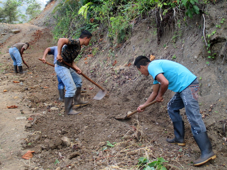 Lote 9 community members dig roadside ditches to prepare for the rainy season. No one else maintains the bumpy rock and dirt access roads. Photo by Sandra Cuffe for Mongabay.