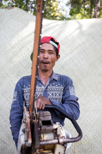 A villager from Mahu poses with his chainsaw in front of one other source of meager local income: a mat made of dry bamboo. Photo by Ann Wang for Mongabay.