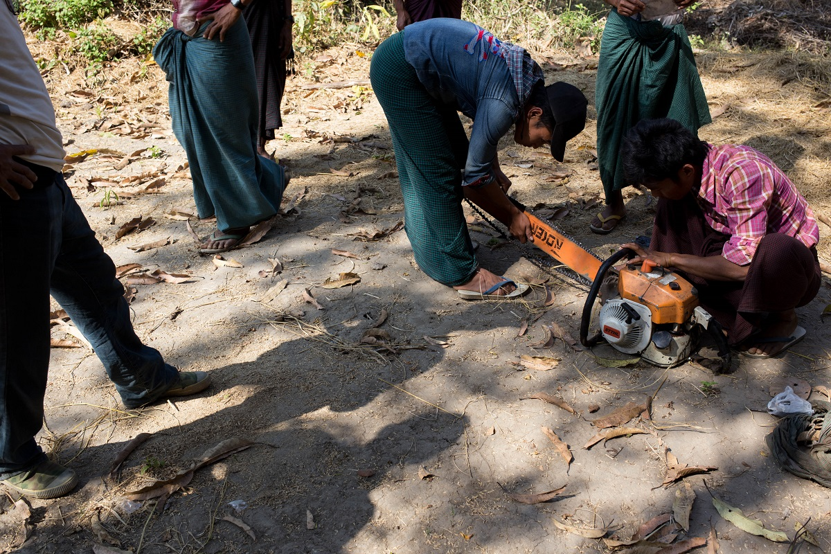 Altered to an inspection by the Forestry Department, villagers from Mahu take a chainsaw apart to hide parts in different locations in the forest. Photo by Ann Wang for Mongabay.