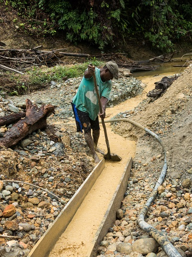 An miner tries to separate rocks from what he is mining for. Photo by Bram Ebus for Mongabay.