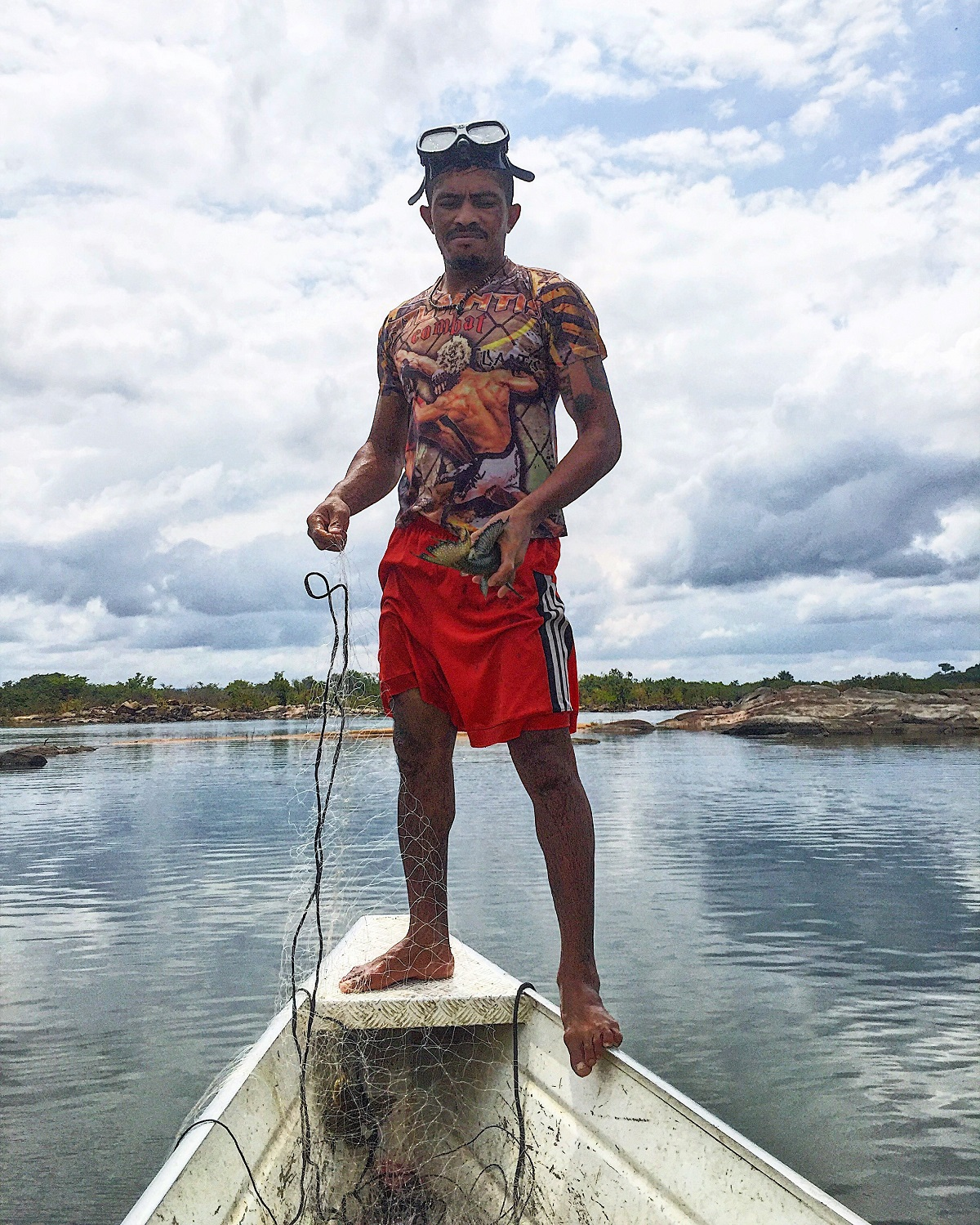 Caboco holds an Acari fish on Sunday fishing trip. Photo by Maximo Anderson for Mongabay.