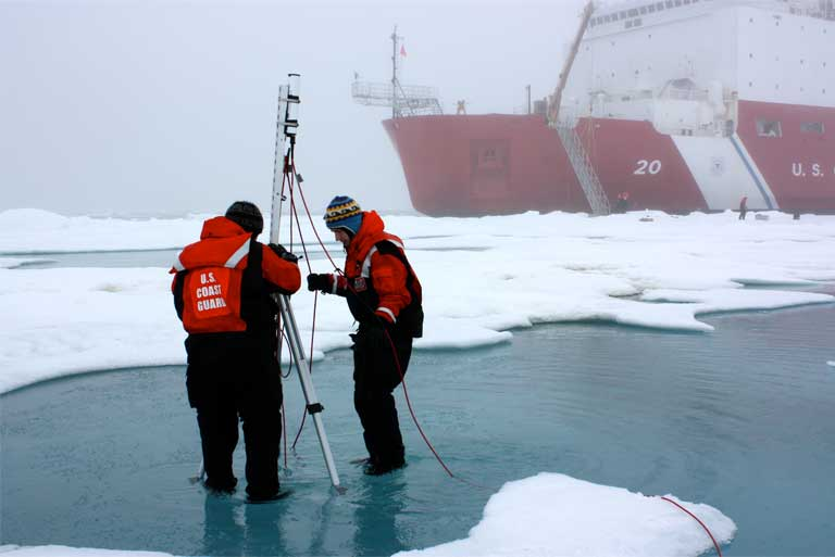 Clark University's Karen Frey and Luke Trusel work amid sea ice in the Chukchi Sea on July 4, 2010, setting up an instrument to measure the optical properties of melt ponds. The research is part of NASA's ICESCAPE mission to sample the physical, chemical and biological characteristics of the ocean and sea ice Photo by Kathryn Hansen/NASA