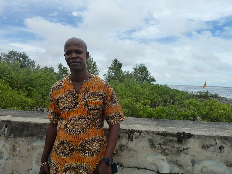 Raymond Hinds against the seawall in Victoria, Guyana. Photo by Carinya Sharples for Mongabay.