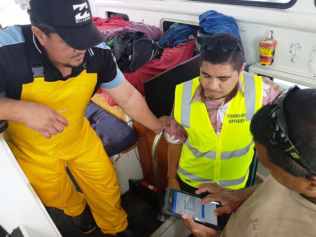 Cook Islands MMR Data Manager Marino Wichman, flanked by tuna fishing captains Thomas Kafoa and Itaaka Atitoa from Ocean Fresh Ltd., Rarotonga, Cook Islands, testing the OnBoard e-Reporting app.