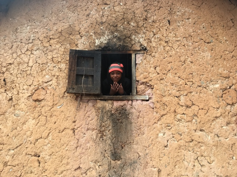 A girl peeks out of a window in the settlement of Ankialo, where all eight homes have been robbed at least once in the last two years. Thieves have knocked out enough bricks to enter through holes in the wall, and used axes to chop through the front door. Photo by Rowan Moore Gerety for Mongabay.